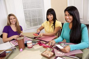 Three mid-adult, multi ethnic ladies scrapbooking together. Photographs and crafts pictured were done by the photographer.